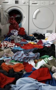 pile of clothes spilling out of a washing machine